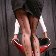 Sexy redhead nylon fetish model Nadja in black full fashioned stockings, white blouse, platform high heels, and a hot short miniskirt. Sitting in a funky chair peeling of some clothe...
