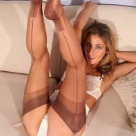 Sexy blonde Sheena Shaw in a matching bra and panty set with garter belt and a pair of brown fully fashioned stockings shows off her nylon legs and feet in...